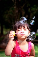 A girl blowing soap bubbles