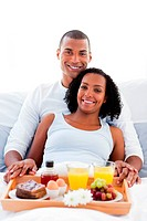 Afro_american couple having breakfast lying on their bed