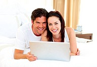 Loving couple using laptop