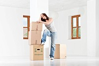 Young woman leaning on cardboard boxes (thumbnail)