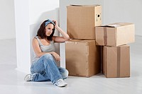 Young woman sitting by cardboard box