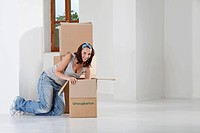 Young woman packing cardboard box, smiling, portrait