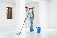 Germany, Bavaria, Young woman mopping floor, smiling, portrait