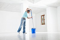 Germany, Bavaria, Young woman mopping floor
