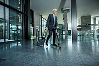 Germany, Stuttgart, Businessman using scooter while pulling luggage in office building
