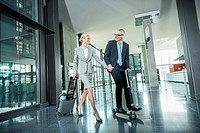 Germany, Stuttgart, Businesswoman with wheeled luggage, man riding scooter at office building (thumbnail)