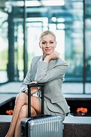Germany, Stuttgart, Businesswoman sitting with wheeled luggage, smiling, portrait