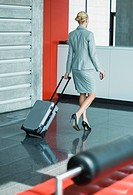 Germany, Stuttgart, Businesswoman walking with wheeled luggage