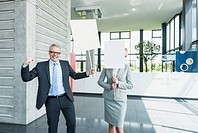 Germany, Stuttgart, Business people holding blank signs in office lobby, smiling