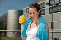 Germany, North_Rhine_westphalia, Duesseldorf, Young woman holding water bottle, smiling, portrait