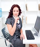 Young businesswoman shushing with her finger in office