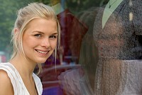 Germany, North Rhine Westphalia, Cologne, Young woman at window shopping, smiling, portrait