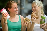Germany, North Rhine Westphalia, Cologne, Young women with coffee and croissants, smiling