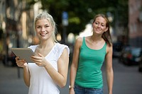 Germany, North Rhine Westphalia, Cologne, Young women with digital tablet on street, smiling