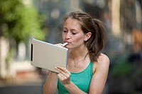Germany, North Rhine Westphalia, Cologne, Young woman using digital tablet as mirror