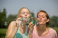 Germany, North Rhine Westphalia, Cologne, Young women blowing soap bubbles