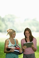 Germany, North Rhine Westphalia, Cologne, Young women with digital tablet and books, smiling