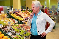 Germany, Cologne, Mature woman thinking in supermarket (thumbnail)