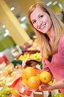 Germany, Cologne, Young woman with smart phone and oranges in supermarket, smiling