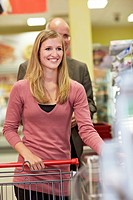 Germany, Cologne, Man and woman waiting in supermarket, smiling (thumbnail)