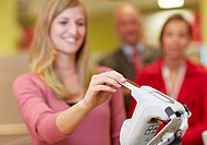 Germany, Cologne, Woman using credit card in supermarket (thumbnail)
