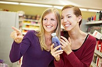 Germany, Cologne, Young women in supermarket, smiling