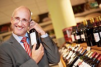 Germany, Cologne, Mature man holding wine bottle in supermarket, smiling, portrait