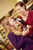 Germany, Cologne, Young women with wine bottles in supermarket