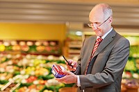Germany, Cologne, Mature man with redcurrant and mobile in supermarket
