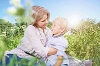 Germany, Cologne, Mother and son sitting on blanket at picnic