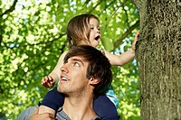 Germany, Cologne, Father carrying daughter on shoulders (thumbnail)