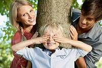 Germany, Cologne, Boy playing hide and seek with parents (thumbnail)