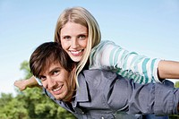Germany, Cologne, Young couple flying, smiling, portrait (thumbnail)