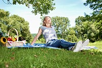 Germany, Cologne, Young woman relaxing at picnic (thumbnail)