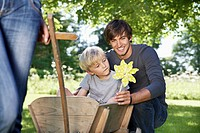 Germany, Cologne, Father and son with paper windmill, smiling