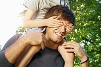 Germany, Cologne, Father carrying son on shoulders, covering his eyes (thumbnail)