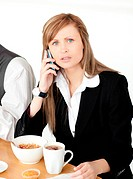 Worried businesswoman talking on phone while having breakfast