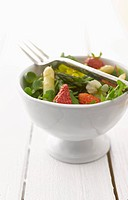 Herbs salad with asparagus and strawberries in bowl, close_up