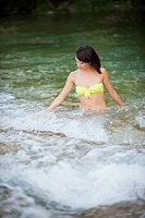 USA, Texas, Leakey, Young woman taking bath in Frio River
