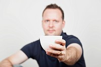 Mid adult man offering coffee, portrait