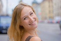 Germany, Bavaria, Munich, Young woman smiling in front of Bavarian State Library at Ludwigstrasse