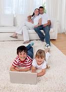 Children using a laptop on floor in living_room