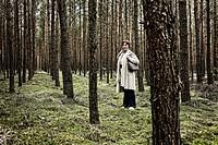 Woman between pine trees