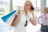 Germany, North_Rhine_Westphalica, Duesseldorf, Businesswoman with shopping bag using smartphone, another woman standing in background