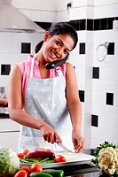 Young woman cutting vegetables and speaking on phone in a kitchen