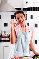 Woman wearing apron standing in kitchen, portrait