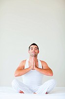 Man sitting on bed doing yoga with copy_space