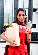 Woman holding a carry bag of fruits and vegetables, and money