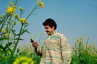 Man standing in fields using the cell phone