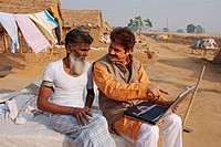 Man showing a laptop to a person in a village